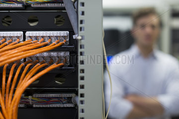 Network cables connected to computer mainframe  computer technician in background