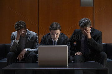 Disappointed business associates sitting side by side on sofa looking at laptop computer