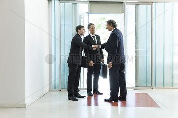 Senior business executive introducing new associate to collegue