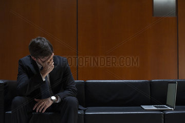 Businessman covering eyes with hand in disbelief