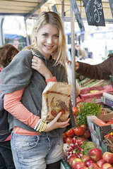 Young woman at greengrocer's buying fresh fruits and vegetables