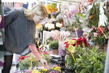 Woman in flower shop browsing bouquet selection