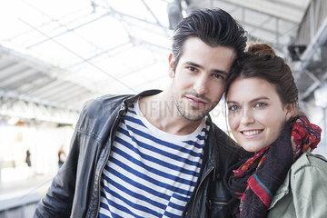 Young couple together on train platform  portrait