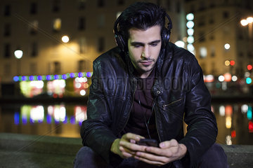 Young man sitting alone outdoors at night listening to music with headphones