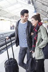 Couple with luggage on train platform