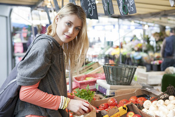 Young woman at greengrocer's shopping for fresh fruits and vegetables