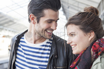 Young couple together on train platform