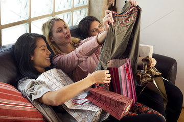 Young women looking at contents of shopping bags together