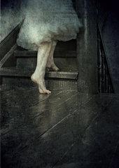Frau barfuss auf einer Holztreppe