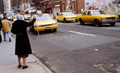 New York - Eine Aeltere Frau winkt ein Taxi in Manhattan