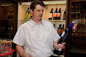 Ober liest Etikette einer Rotweinflasche