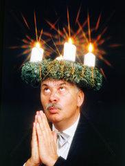 betender Mann mit Adventskranz auf dem Kopf