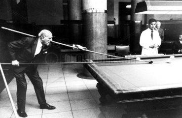 Mann spielt mit langem Queue Billiard