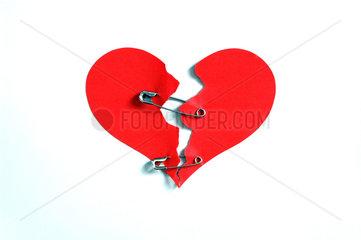 Sicherheitsnadeln halten zerrissenes Herz zusammen