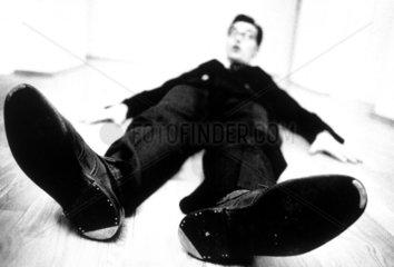 Mann liegt flach auf dem Boden