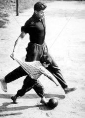 Vater und Sohn rennen um den Ball