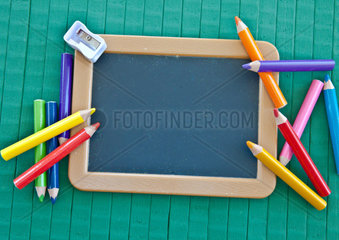 Hintergrund zum Schulanfang mit Tafel und bunten Stiften