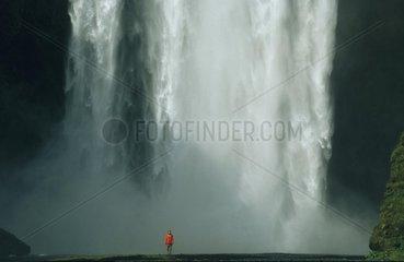 Frau steht vor riesigem Wasserfall