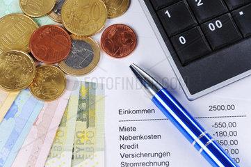 Euroscheine und Muenzen mit Kugelschreiber  Tabelle und Taschenrechner