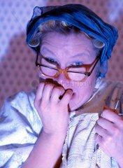 Hausfrau kaut Fingernaegeln