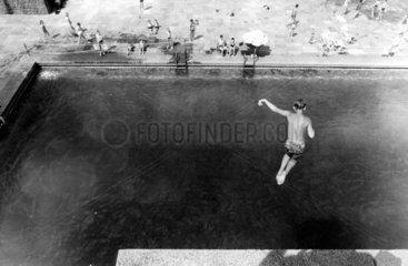 Junge springt in den Pool.