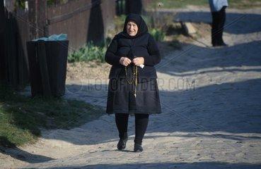 alte Frau in Schwarz mit Rosenkranz