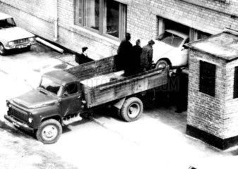 Drei Maenner verladen Auto
