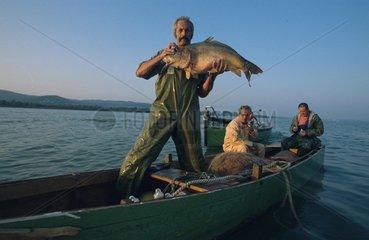 Fischer zeigt stolz seinen grossen Fang