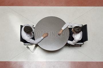 Businessmen stting opposite each other