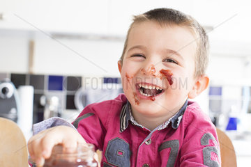 Little boy with jam on his face laughing