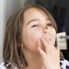 Girl with chocolate smeared on her nose  licking fingers