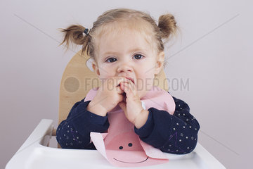 Baby girl sitting in high chair  chewing on fingers