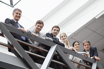 Team of executives standing together on balcony