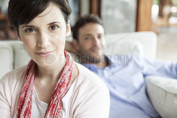 Woman sitting in living room with husband in background  portrait