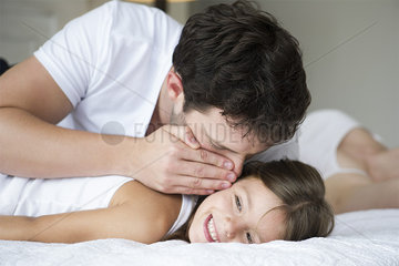 Father whispering to young daughter