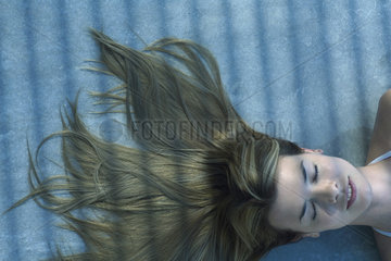 Woman lying in shade with her hair spread out on the ground