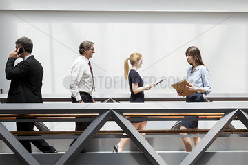 Business professionals walking through corridor
