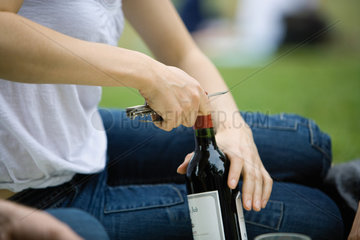Woman uncorking bottle of wine outdoors  cropped