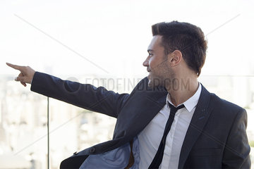 Businessman on rooftop  pointing at view