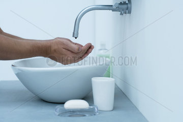 Man holding hands under dripping faucet in bathroom sink  cropped