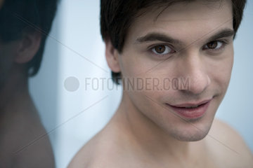 Young man with bare shoulders  smiling  portrait