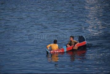 zwei Jungs in einem kleinen sinkenden Boot