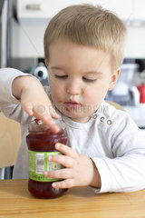 Toddler boy eating jam from jar with his finger
