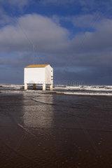 Stilt building on beach during high tide