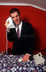 Mann verwechselt Telefon mit Buegeleisen