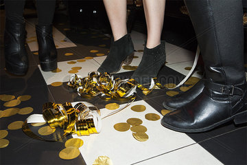 People dancing at night club with confetti and streamers on dance floor