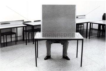 Mann sitzt in einer Wahlkabine