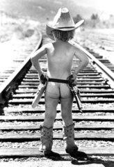 Nackter Cowboy auf den Schienen