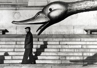riesiger Entenkopf ueber einem Mann