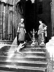 Zwei Putzfrauen spritzen Jesus ab